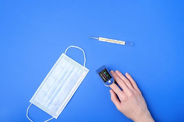 Persoon die pulsoximeter-apparaat op vinger gebruikt in de buurt van thermometer en medisch masker, gezondheidszorgmonitoringconcept