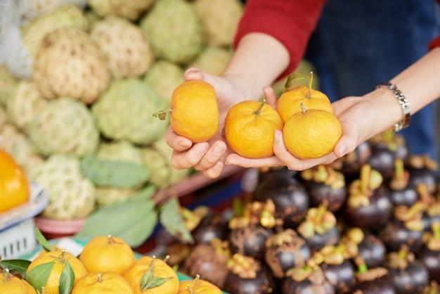 Persoon die rijpe mandarijnen koopt