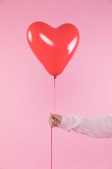 Persoon die rode ballon met draad houdt