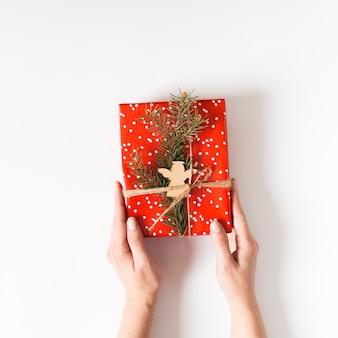 Persoon die rode geschenkdoos in handen