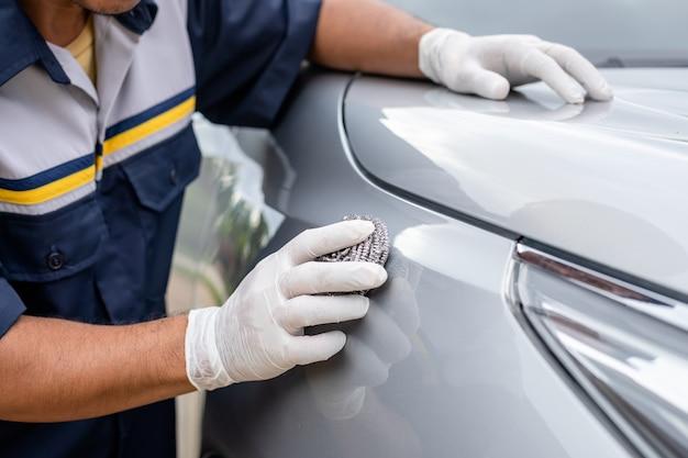 Persoon die roestvrij staalwol gebruikt om het oppervlak van een auto te polijsten