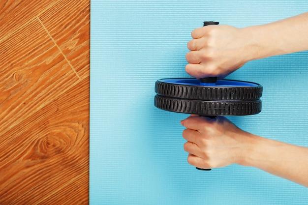 Persoon die rol op blauwe mat gebruikt