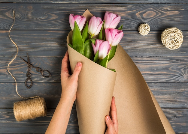 Persoon die roze tulpen in pakpapier verpakken