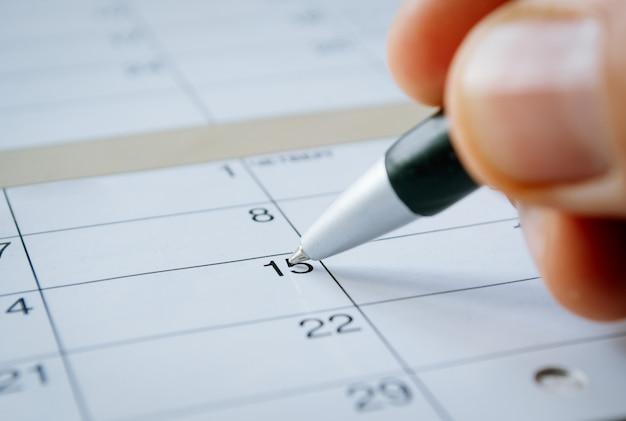 Persoon die schrijft op een kalenderdatum van de 15e