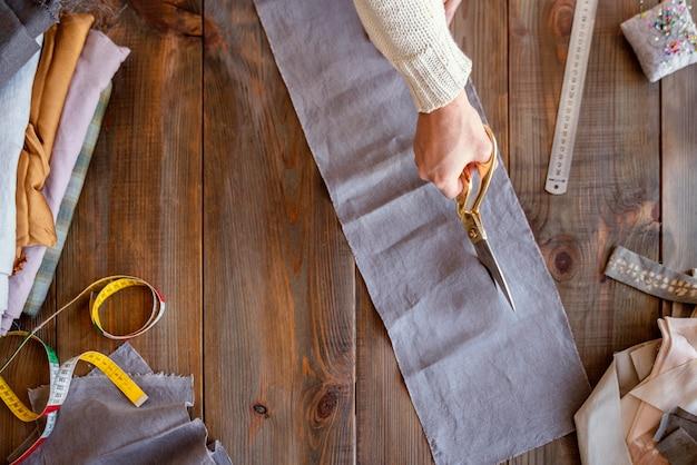 Persoon die stof snijdt om te naaien