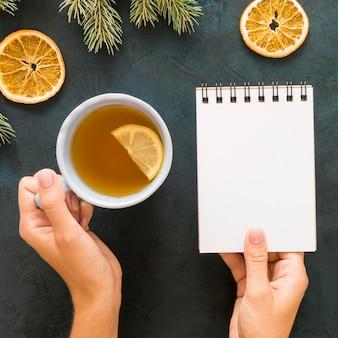 Persoon die thee drinkt en een leeg notitieboekje houdt