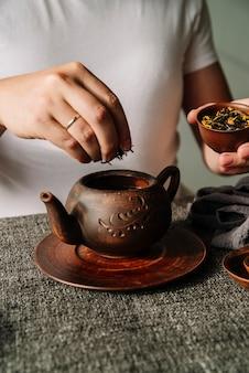 Persoon die theekruiden in een theepot zet