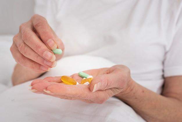 Persoon die veel kleurrijke pillen houdt