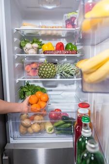 Persoon die verse sinaasappelen uit de koelkast neemt