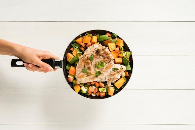 Persoon die versierde vleesfilet in pan houdt