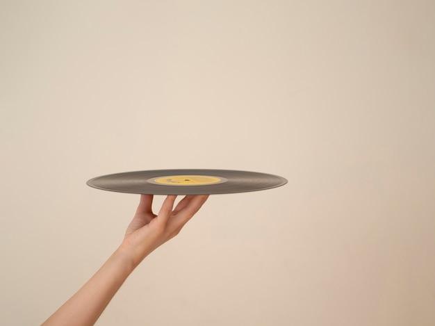 Persoon die vinylschijf met exemplaar-ruimte steunt