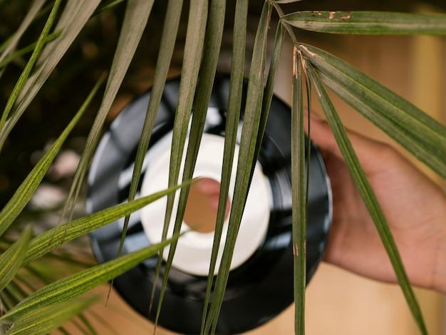 Persoon die vinylverslag achter een blad houdt