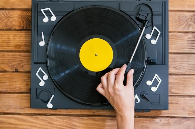 Persoon die vinylverslag in speler speelt