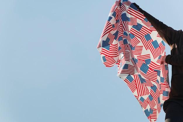 Persoon die vlaggen van de vs zwaaien