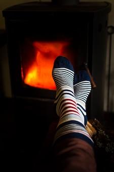 Persoon die voeten naast het vuur opwarmt