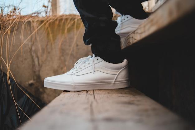 Persoon die witte lage sneakers draagt