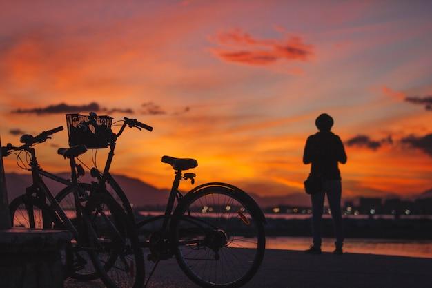Persoon die zich bij fiets in zonsondergang bevindt