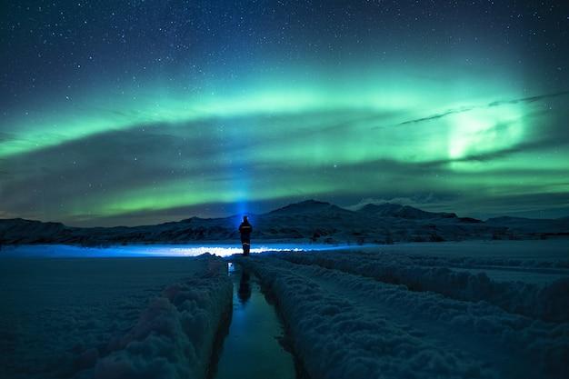 Persoon die zich op besneeuwde grond onder groene hemel bevindt