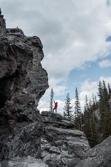 Persoon die zich op rotsachtige heuvel bevindt en rechterhand naast bomen opheft onder witte en grijze luchten