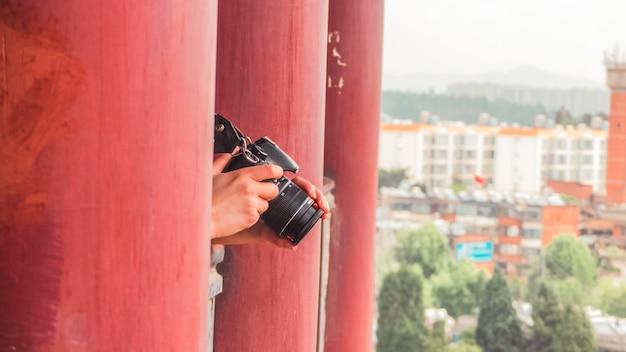 Persoon die zich tussen rode pijlers bevindt en camera vasthoudt