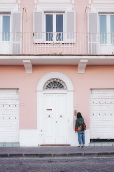 Persoon die zich voor roze en wit geschilderd gebouw bevindt