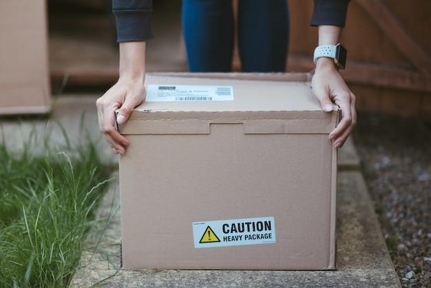 Persoon die zijn armen op een kartonnen doos rust met een label