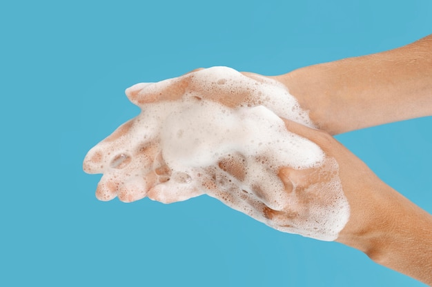 Persoon die zijn handen met blauwe achtergrond wast