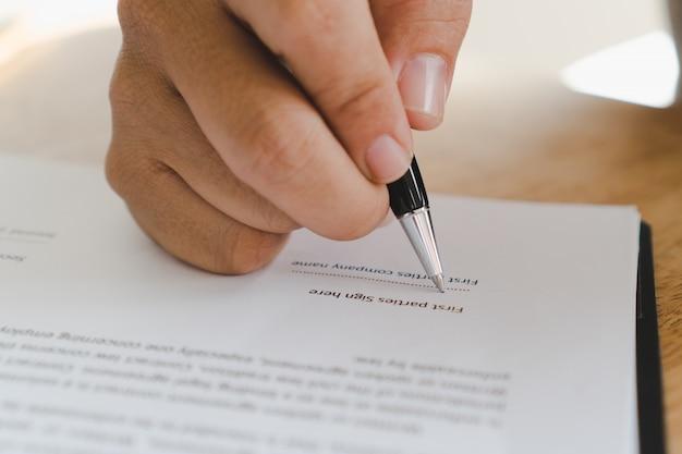 Persoon die zijn naam ondertekent in document.