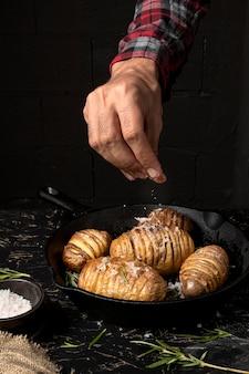 Persoon die zout over aardappels in pan bestrooit