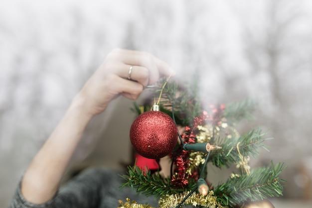 Persoon door een raam opknoping kerstversiering aan de boom met een rode kerstbal in hun hand en reflecties op het glas.