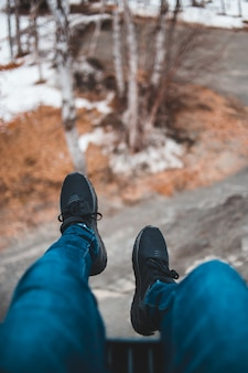 Persoon draagt blauwe denim jeans en zwarte sneakers