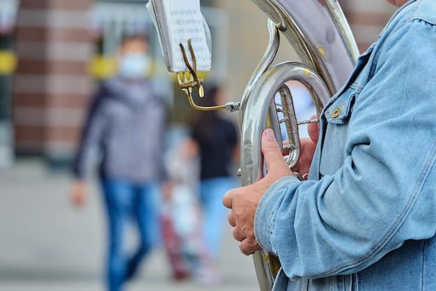Persoon een muziekinstrument-trompet spelen op straat in de zomer.