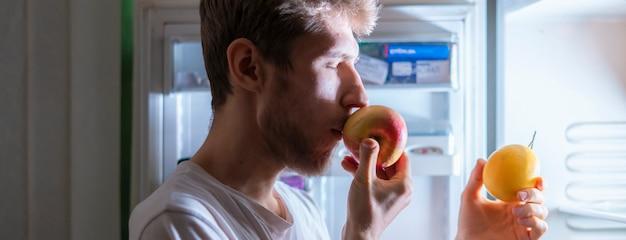 Persoon eet 's avonds laat gezond fruit uit de koelkast f
