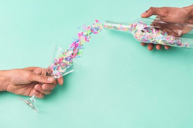Persoon gieten confetti uit de fles in het glas