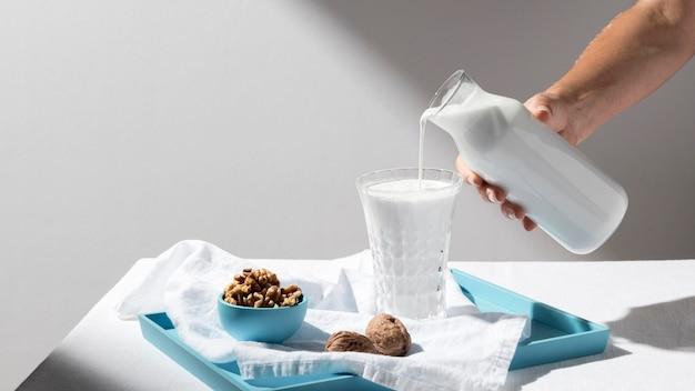 Persoon gieten melk in vol glas met walnoten op dienblad