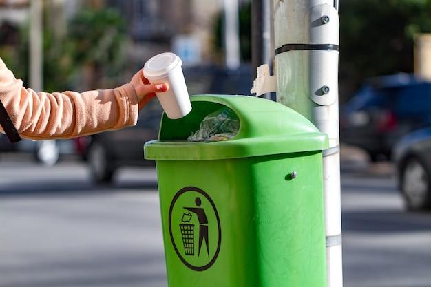 Persoon gooit een papieren koffiekopje in de vuilnisbak