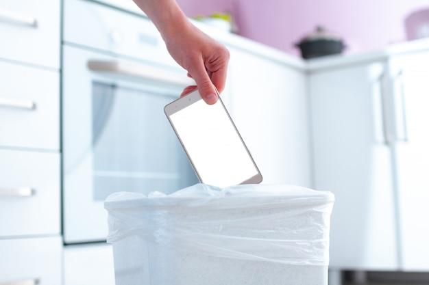 Persoon gooit telefoon in de prullenbak. verslaving aan telefoon, internet en sociale netwerken. digitale verslaving en telefoonuitgang