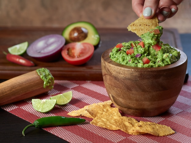 Persoon guacamole eten met maïs toast groenten en chili