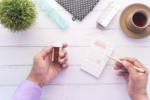 Persoon hand met pil container en kalender