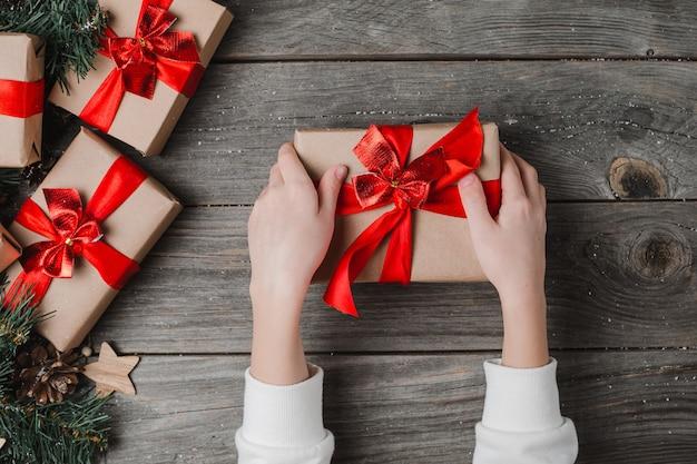 Persoon handen houden kerstcadeau houten oppervlak. xmas gift boxes handgemaakte tag wrapping overhead view. Premium Foto