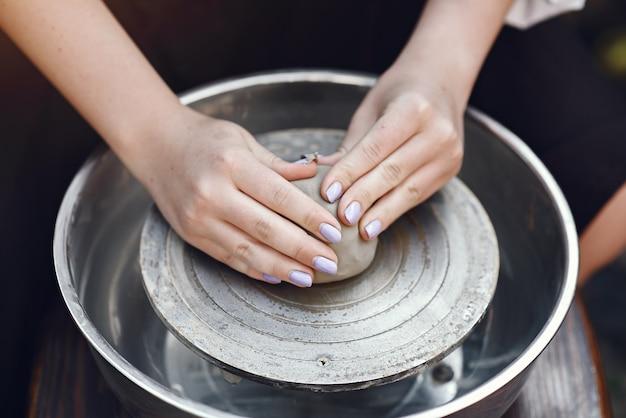 Persoon het spelen met klei op de aardewerkmachine