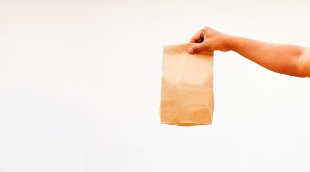 Persoon houdt bruine lege ambachtelijke papieren zak voor afhaalmaaltijden