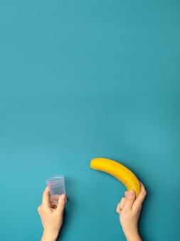 Persoon houdt een plastic container en een banaan