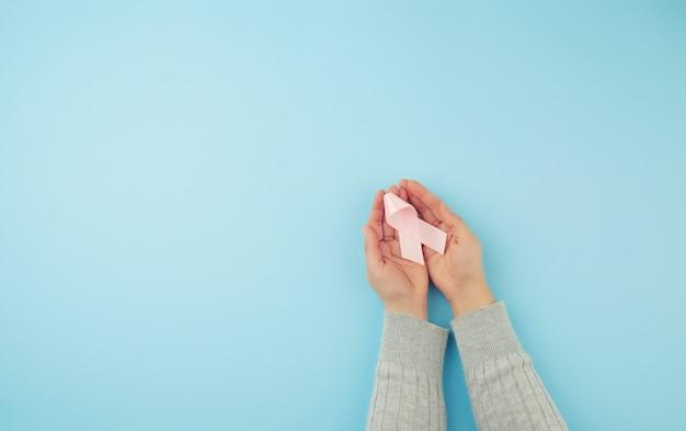 Persoon houdt een roze boogvormig lint op een blauwe ondergrond