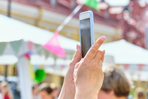 Persoon houdt een smartphone op straat en maakt een foto.
