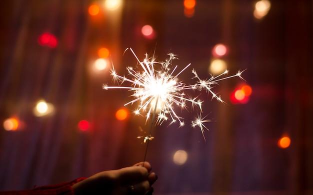 Persoon houdt een sterretjesstokje in een hand. festival wonderkaarsen. gelukkig nieuwjaar.