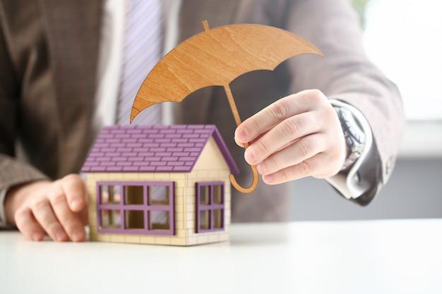 Persoon houdt houten paraplu over huis