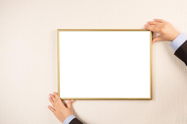 Persoon houdt mockup-fotolijst aan de muur