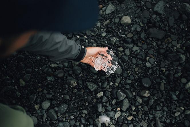 persoon houdt stuk gletsjerijs in ijsland