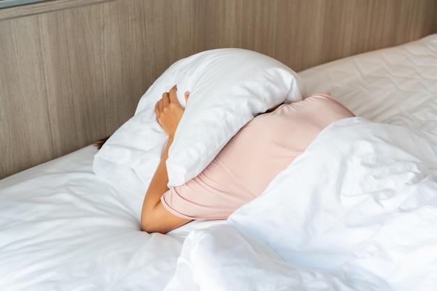 Persoon in bed die een kussen gebruikt om haar hoofd te bedekken om zich te verbergen voor het zonlicht